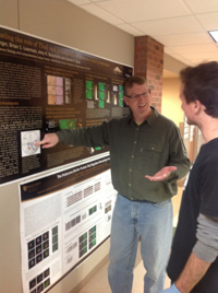 Darren Seals with a student looking at a research poster